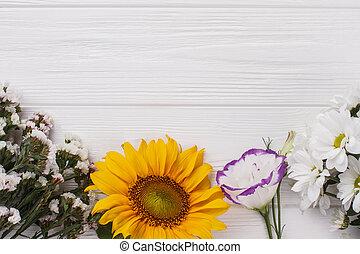 Variedad de flores en madera blanca.