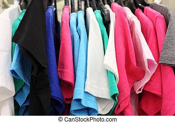 Variedad de ropas casuales multicolores en la tienda, camisetas colgando de perchas