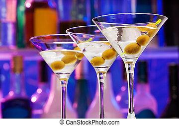 Varios vasos de cóctel con aceitunas en el bar