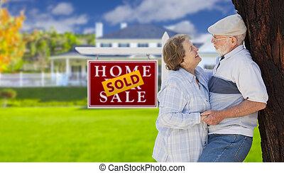 Vendí un letrero de bienes raíces con una pareja mayor en frente de la casa