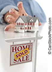 Vendido de bienes raíces al frente, una mujer buscando casa