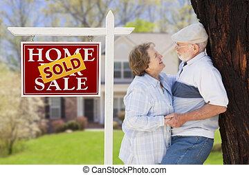 Vendido de bienes raíces con pareja de ancianos frente a casa