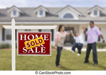 Vendido de bienes raíces y familia hispana frente a la casa