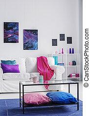 Vertical vista de la sala de estar con estilo cómodo sofá blanco con manta rosa y almohadas azules y púrpuras, gráficos cosmos en la pared, foto real