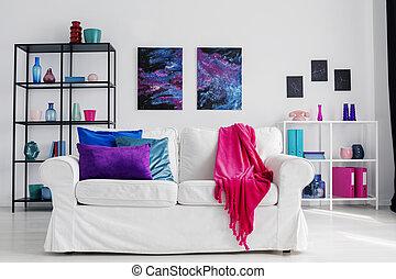 Vertical vista de sala de estar con estilo cómodo sofá blanco con manta rosa y almohadas azules y púrpuras, gráficos cosmos en la pared y estanterías de metal con accesorios, fotos reales