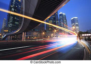 Viaducto urbano de noche de autos con senderos de luz del arco iris