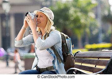 Viajera femenina tomando fotos con cámara digital