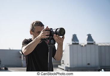 Videógrafo profesional usando cámara de video digital.