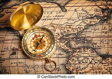 Vieja brújula dorada en un mapa antiguo