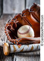 Viejo bate de béisbol y guante con bola