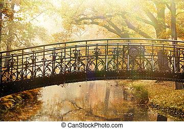 Viejo puente en el parque de nieblas de otoño