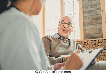 Viejo sabio teniendo una conversación cómoda con la enfermera