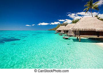 Villas en la playa tropical con escaleras en el agua