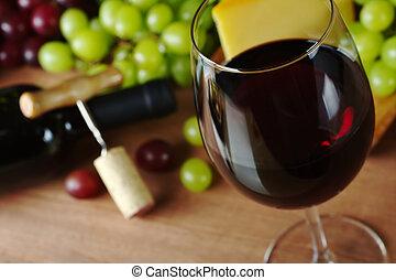 Vino tinto en vasos de vino con uvas, queso una botella de vino y un sacacorchos con corcho en el fondo (Concéntrese en el frente del borde de la copa de vino)