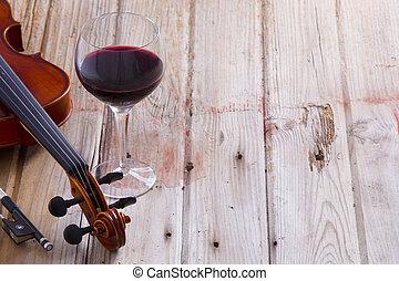Violín y vino en suelo de madera con espacio de copiado