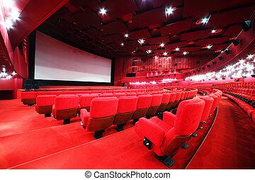 Vista desde las escaleras en pantalla y filas de cómodas sillas rojas en el cine de la sala roja