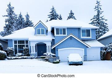 Vista frontal de casa durante la nevada de invierno