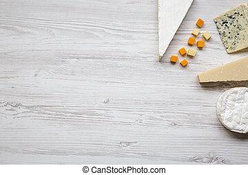 Vista superior, conjunto de varios quesos en un fondo blanco de madera. Copia espacio. Comida para el vino. De plano, desde arriba.