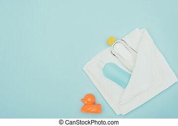 Vista superior de accesorios de baño en toalla y pato de goma aislado en azul