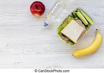 Vista superior, saludable almuerzo escolar con sándwiches, frutas y botella de agua en fondo blanco de madera, plano. Desde arriba. Copia espacio.