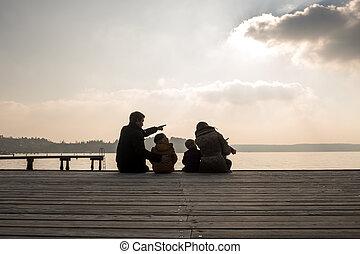 Vista trasera de la familia al aire libre mirando el mar