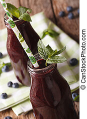Zumo de arándano orgánico en una botella de vidrio macro. Vertical